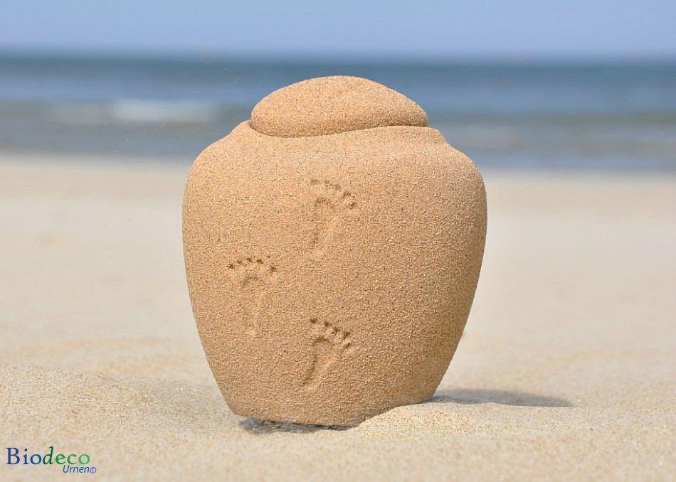 Biologisch afbreekbare mini zee-urn met voetafdrukken in het zand,
