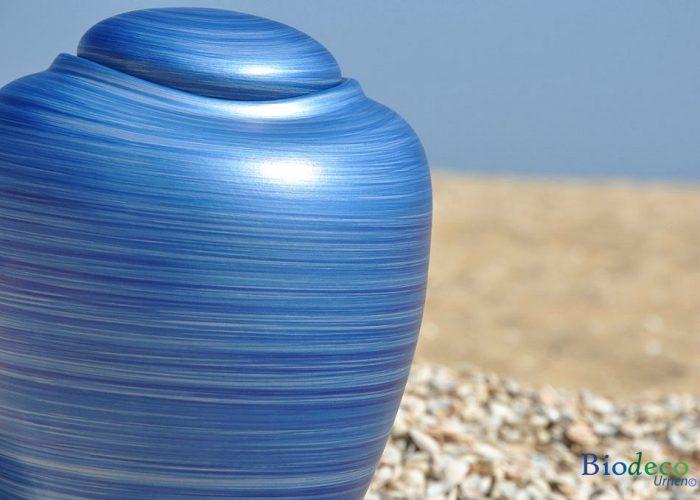 Detail van de bio-urn Ocean Aqua, biologisch afbreekbaar op een schelpen strand