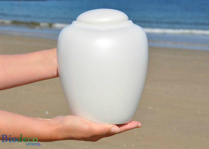 Bio-urn Ocean parel, biologisch afbreekbare urn in handen op het strand