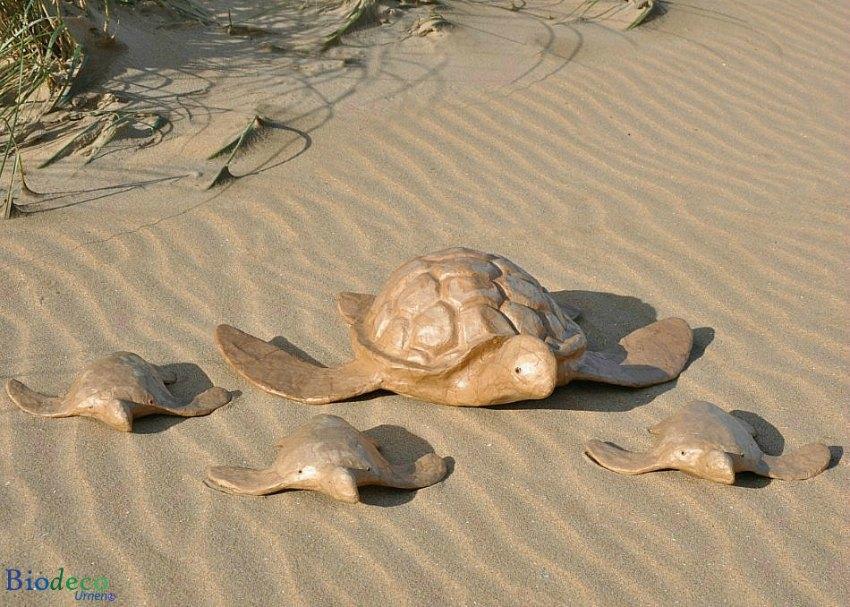 De zee-urn Schildpad op het strand van Scheveningen, handvervaardigd van gerecycled papier, omringd door drie mini Schildpad zee-urnen