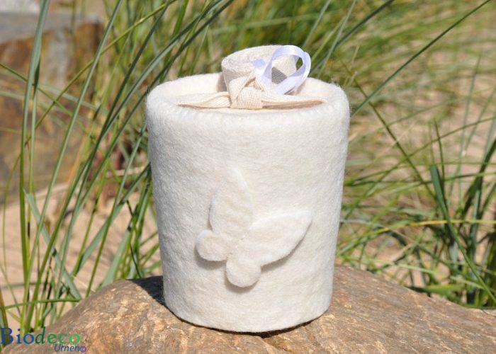 De biologisch afbreekbare mini vilt-urn Vlinder Roomwit, gedecoreerd met een vilten vlinder, voor een asbijzetting in de aarde